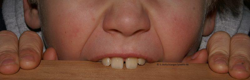 Zähne beißen auf einen Tisch