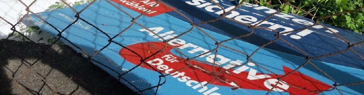 Ein AfD-Plakat hinter Maschendrahtzaun
