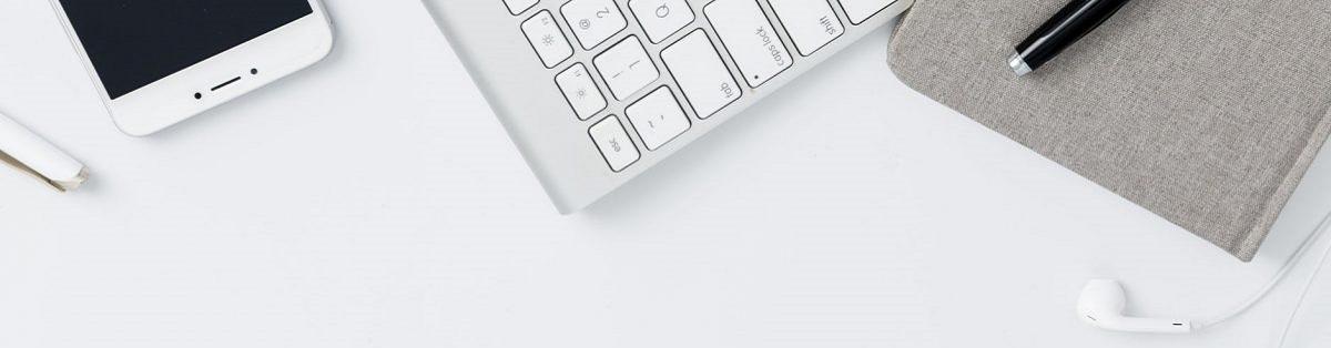 Laptop, Handy, Notizblock und Kopfhörer liegen auf weißem Untergrund